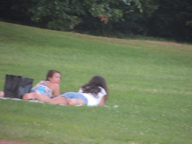 girls lying on grass together, images