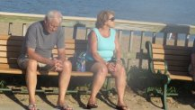 couple sitting on bench,on boardwalk-images