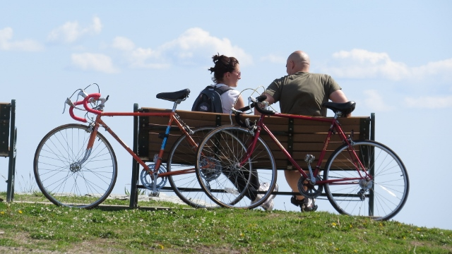 couple with bicycle sitting on bench,images