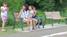 mother sitting on bench with children,images