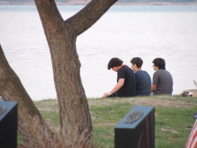 teen boys sitting on beach,policy