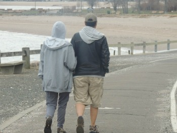couples on the boardwalk hugging while walking
