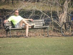 man sitting cross legged in park,images