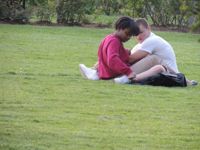 young interracial couple sitting on grass,love display